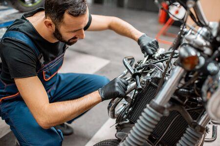 Hombre guapo en ropa de trabajo ajustando las válvulas del motor de una hermosa motocicleta vintage en el taller
