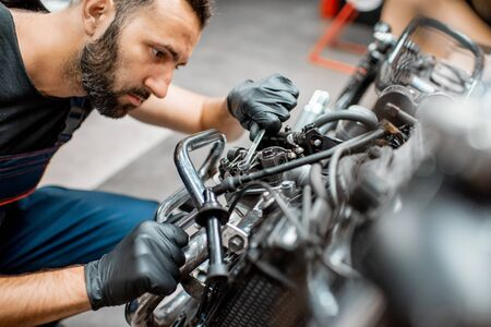 Handsome man in workwear adjusting engine valves of a beautiful vintage motorcycle at the workshop