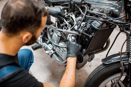 Gut aussehender Mann in Arbeitskleidung, der die Motorventile eines schönen Oldtimer-Motorrads in der Werkstatt einstellt
