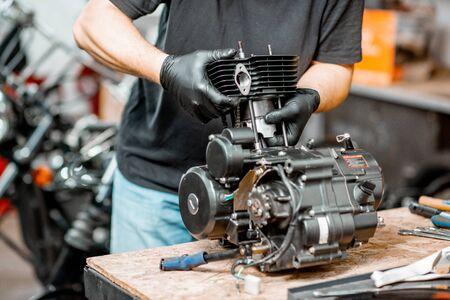 Obrero desmontando el motor de la motocicleta durante una reparación en la mesa de trabajo del taller, primer plano sin rostro Foto de archivo