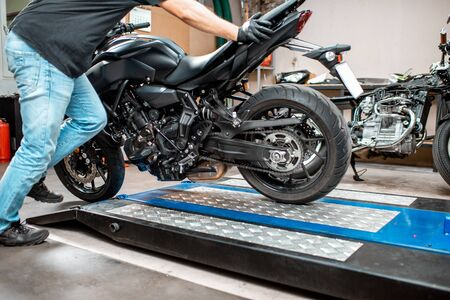 Worker putting motorcycle on a lift, preparing for the repairment in the workshop Imagens