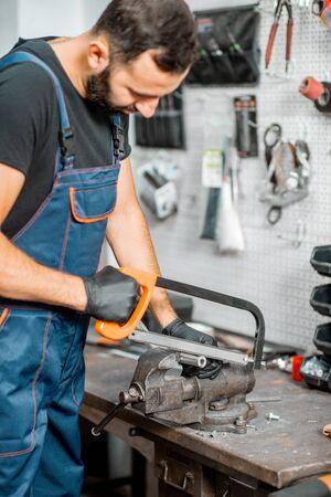 Handwerker im Overall, der Metallrohre mit Bügelsäge schneidet oder etwas in der Werkstatt repariert Standard-Bild