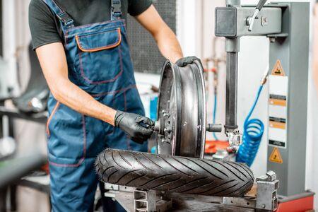 Operaio di servizio che cambia pneumatico per motocicletta su un'attrezzatura speciale per l'installazione di pneumatici in officina, primo piano senza volto