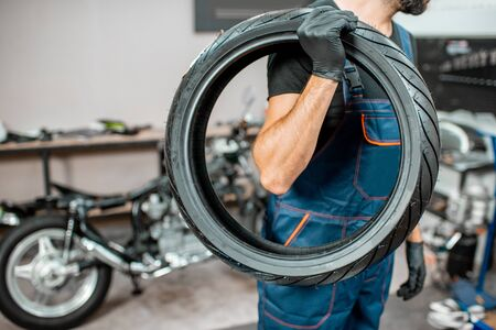 Service worker in overalls carrying motorcycle tire for changing at the workshop
