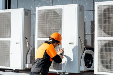 Facharbeiter in Schutzkleidung, der das Außengerät der Klimaanlage oder Wärmepumpe auf dem Dach installiert oder repariert