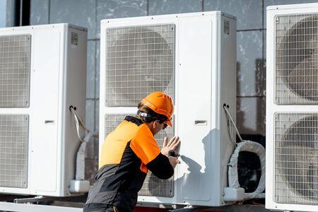 Professionele werkman in beschermende kleding die de buitenunit van de airconditioner of warmtepomp op het dak installeert of repareert