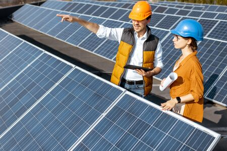 Two engineers or architects examining the construction of a solar power plant, standing with digital tablet between rows of solar panels