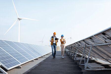 Uitzicht op de zonne-energiecentrale op het dak met twee ingenieurs die lopen en fotovoltaïsche panelen onderzoeken. Concept van alternatieve energie en zijn service