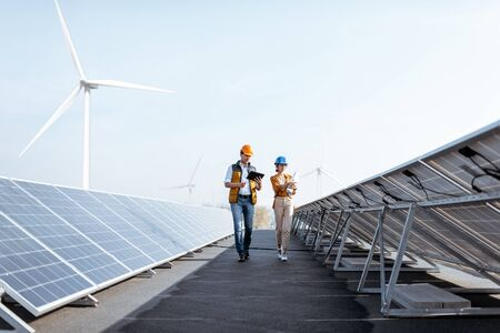 View on the rooftop solar power plant with two engineers walking and examining photovoltaic panels. Concept of alternative energy and its service Stockfoto - 133475753