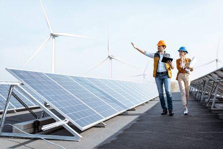Widok na elektrownię słoneczną na dachu z dwoma inżynierami spacerującymi i badającymi panele fotowoltaiczne. Koncepcja energii alternatywnej i jej obsługa