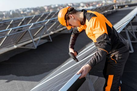 Well-equipped worker in protective orange clothing installing or replacing solar panel on a photovoltaic rooftop plant. Concept of maintenance and installation of solar stations
