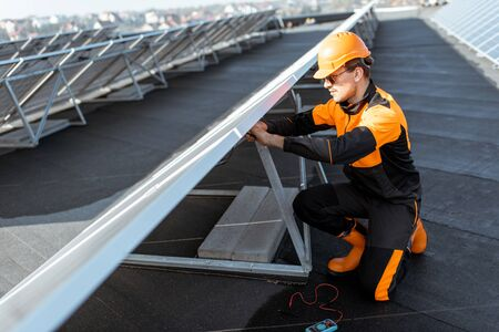 Well-equipped electrician connecting wires of solar panels on a rooftop photovoltaic power plant. Concept of installing solar stations