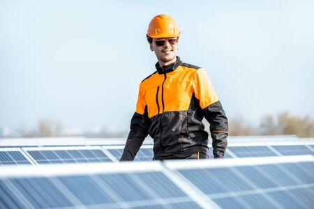 Well-equipped worker in protective orange clothing examining solar panels on a photovoltaic rooftop plant. Concept of maintenance and installation of solar stations