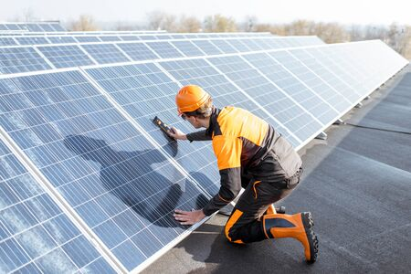 Well-equipped worker in protective orange clothing installing solar panels, measuring the angle of inclination on a photovoltaic rooftop plant