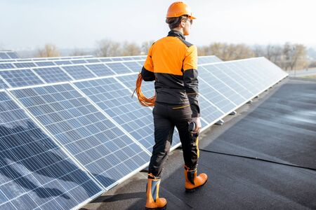 Well-equipped worker in protective orange clothing walking and examining solar panels on a photovoltaic rooftop plant. Concept of maintenance and installation of solar stations Reklamní fotografie
