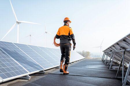 Operaio ben attrezzato in abbigliamento protettivo arancione che cammina ed esamina i pannelli solari su un impianto fotovoltaico sul tetto. Concetto di manutenzione e installazione di stazioni solari