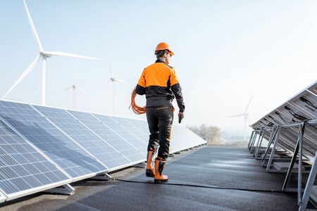 Well-equipped worker in protective orange clothing walking and examining solar panels on a photovoltaic rooftop plant. Concept of maintenance and installation of solar stations