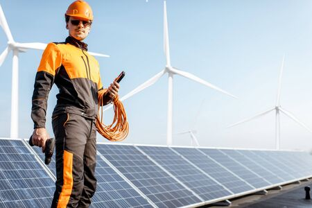 Portrait of a well-equipped worker in protective orange clothing examining solar panels on a photovoltaic rooftop plant. Concept of maintenance and installation of solar stations