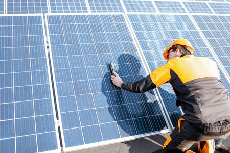 Well-equipped worker in protective orange clothing installing solar panels, measuring the angle of inclination on a photovoltaic rooftop plant 版權商用圖片