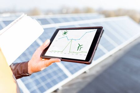 Man with digital tablet on a solar station, close-up on a tablet screen with a chart of solar and wind power daily generation. Concept of online monitoring of the electric station Reklamní fotografie