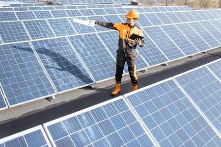View on the rooftop solar power plant with engineer in protective workwear walking and examining photovoltaic panels. Concept of alternative energy and its maintenance Standard-Bild - 133497057