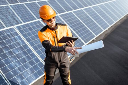 Portrait of an engineer in protective workwear carrying out service of solar panels with digital tablet and blueprintson a photovoltaic rooftop plant Standard-Bild - 133497058