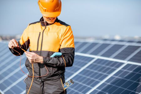 Well-equipped electrician connecting solar panels, checking the voltage and connecting wiring on a rooftop photovoltaic power plant Standard-Bild - 133497062