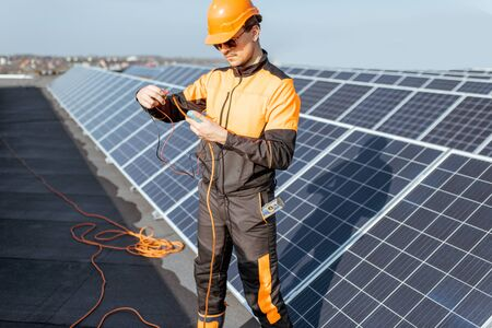 Well-equipped electrician connecting solar panels, checking the voltage and connecting wiring on a rooftop photovoltaic power plant