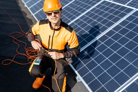 Well-equipped electrician connecting solar panels, checking the voltage and connecting wiring on a rooftop photovoltaic power plant Standard-Bild - 133497064