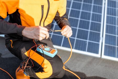 Well-equipped electrician connecting solar panels, checking the voltage and connecting wiring on a rooftop photovoltaic power plant Standard-Bild - 133497065