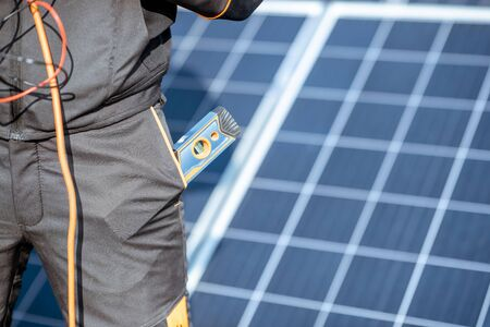 Close-up on a working tools in the pocket of a workman with a solar panels on the background