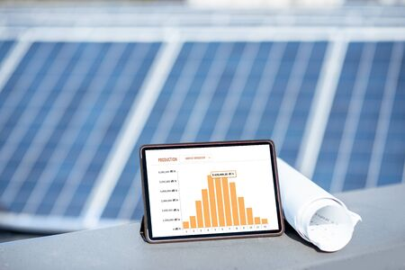 Composition of blueprints and digital tablet with a chart of electricity production on a solar power plant outdoors. Electricity production monitoring concept Standard-Bild - 133497067