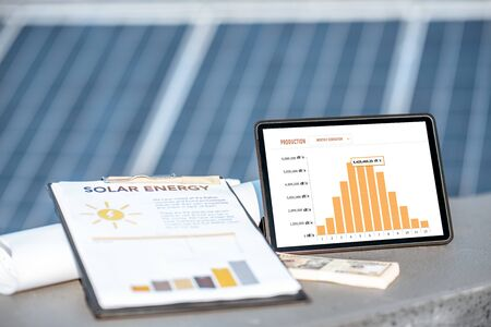 Composition of drawings and digital tablet with a chart of electricity production on a solar power plant outdoors. Electricity production monitoring concept