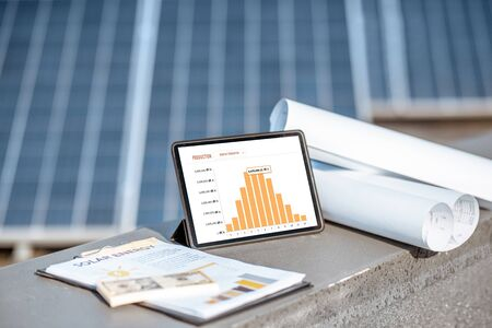 Composition of blueprints, money and digital tablet with a chart of electricity production on a solar power plant outdoors. Electricity production monitoring concept Standard-Bild - 133497069