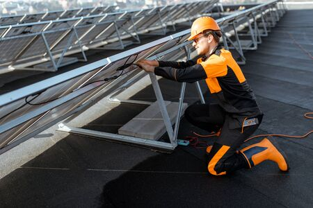 Well-equipped electrician connecting wires of solar panels on a rooftop photovoltaic power plant. Concept of installing solar stations Standard-Bild - 133497070