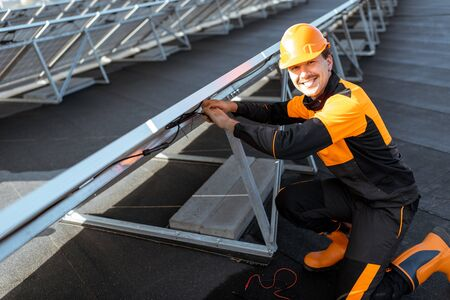 Well-equipped electrician connecting wires of solar panels on a rooftop photovoltaic power plant. Concept of installing solar stations Standard-Bild - 133497071
