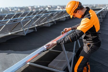 Well-equipped worker in protective orange clothing installing or replacing solar panel on a photovoltaic rooftop plant. Concept of maintenance and installation of solar stations Standard-Bild - 133497072