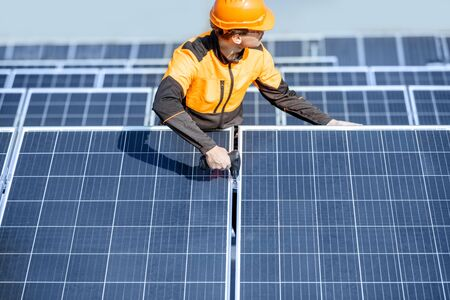 Well-equipped worker in protective orange clothing installing or replacing solar panel on a photovoltaic rooftop plant. Concept of maintenance and installation of solar stations Standard-Bild - 133497074