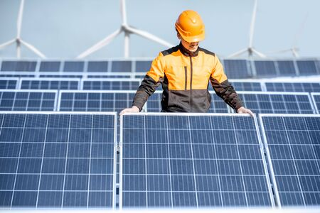 Well-equipped worker in protective orange clothing installing or replacing solar panel on a photovoltaic rooftop plant. Concept of maintenance and installation of solar stations Standard-Bild - 133503625