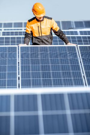 Well-equipped worker in protective orange clothing installing or replacing solar panel on a photovoltaic rooftop plant. Concept of maintenance and installation of solar stations Standard-Bild - 133503626