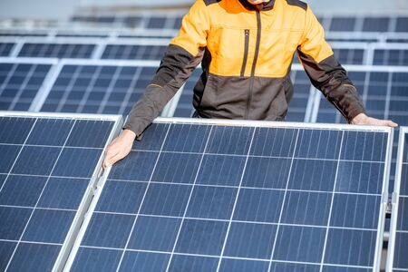 Workman installing or replacing solar panel on a photovoltaic rooftop plant, close-up Concept of maintenance and installation of solar stations Standard-Bild - 133518751