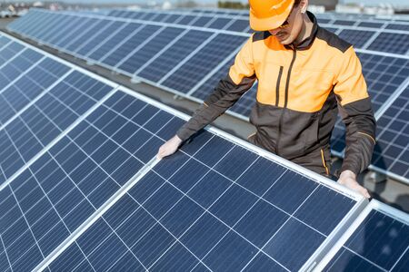 Well-equipped worker in protective orange clothing installing or replacing solar panel on a photovoltaic rooftop plant. Concept of maintenance and installation of solar stations Standard-Bild - 133503631