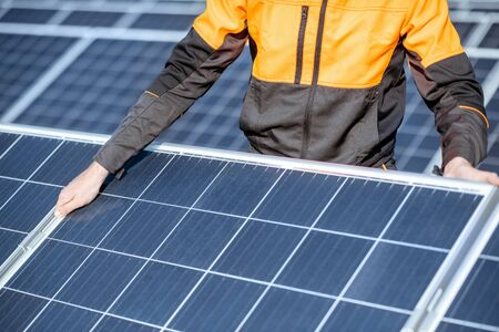 Workman installing or replacing solar panel on a photovoltaic rooftop plant, close-up Concept of maintenance and installation of solar stations Standard-Bild - 133518752