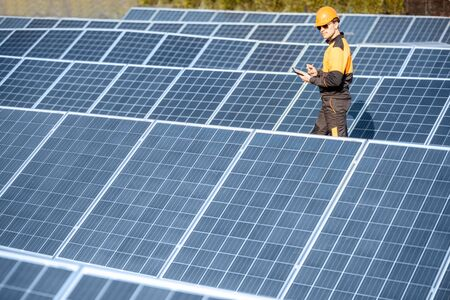 View on the rooftop solar power plant with engineer in protective workwear walking and examining photovoltaic panels. Concept of alternative energy and its maintenance Standard-Bild - 133503646
