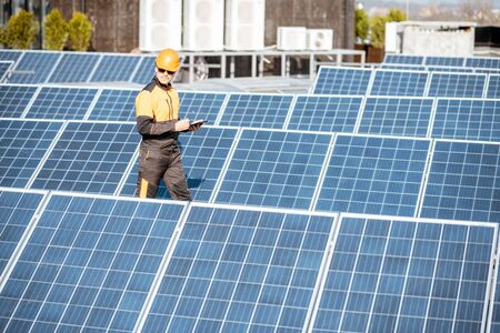 View on the rooftop solar power plant with engineer in protective workwear walking and examining photovoltaic panels. Concept of alternative energy and its maintenance Standard-Bild - 133503648