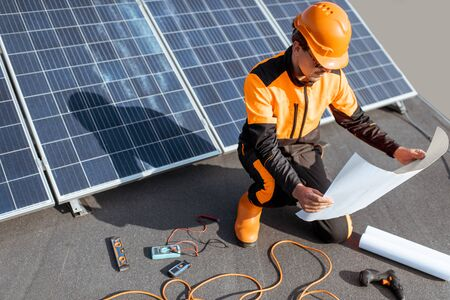 Electrician in protective workwear installing solar panels, sitting on a rooftop with blueprints and working tools Standard-Bild - 133503650