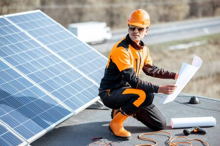 Electrician in protective workwear installing solar panels, sitting on a rooftop with blueprints and working tools Standard-Bild - 133503649