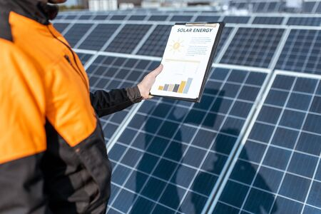 Workman holding a drawing with chart of electricity production on a solar power plant. Concept of solar power plant performance and production Reklamní fotografie