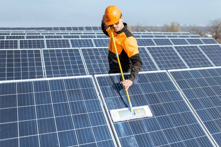 Professional cleaner in protective workwear cleaning solar panels with a mob. Concept of solar power plant cleaning service Standard-Bild - 133503651