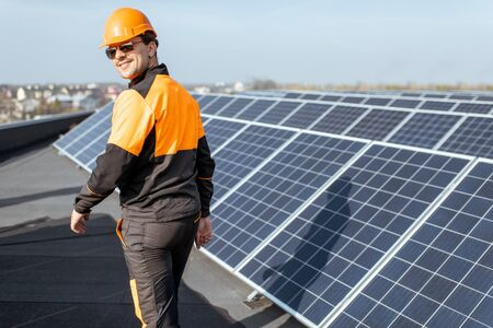 Well-equipped worker in protective orange clothing examining solar panels on a photovoltaic rooftop plant. Concept of maintenance and installation of solar stations Standard-Bild - 133503652